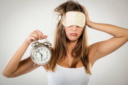 trøtt kvinne med vekkerklokke