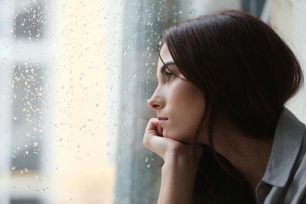 Ei kvinne ser ut av vinduet