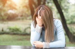 Trist kvinne sitter med hodet skjult i hendene.