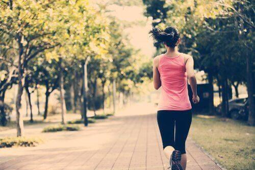 Ryggen til en kvinne som løper gjennom en park