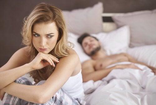 Bekymret kvinne sitter opp i sengen
