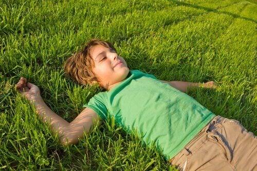 Liten gutt legger seg i gresset med et smil om munnen