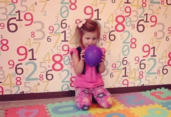 Liten jente som praktiserer ballongpusting