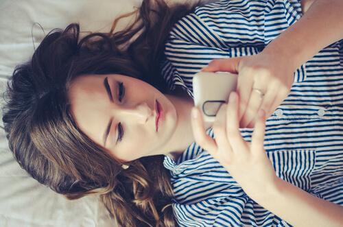 Ung jente ligger på en seng og sjekke sin mobiltelefon, er sosiale medier en del av moderne tvangslidelser
