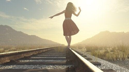 Kvinne balanserer på jernbaneskinner ute i naturen