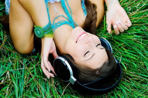 Smilende kvinne ligger i gresset og hører på musikk