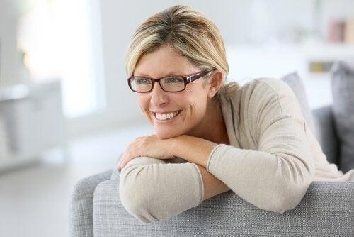 Moden kvinne smiler i sofaen