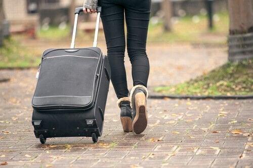 Kvinne i boomeranggenerasjon går med koffert