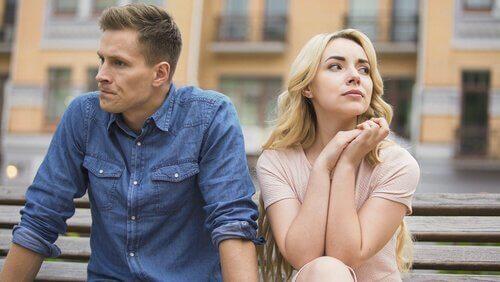 Par sitter på benk og kikker hver sin vei