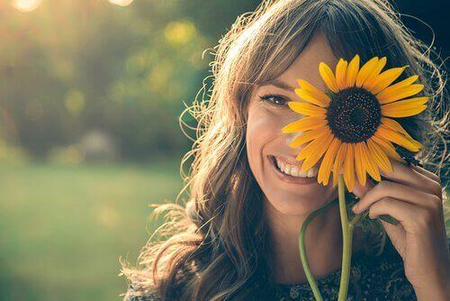 Smilende kvinne holder opp en solsikke