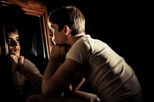 Merkelige følelser en tenåringsgutt ser ettertenksomt på sitt eget speilbilde.l.