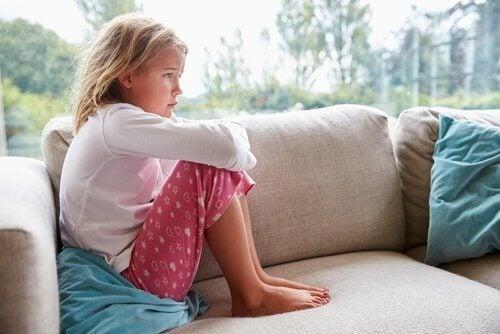 Trist jente på sofaen