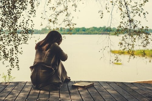 Trist kvinne på en brygge ved en innsjø