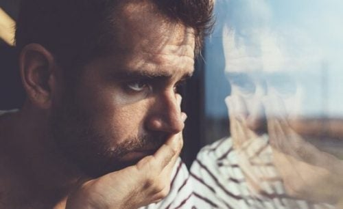 Trist mann ser ut av vinduet