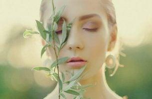 Ung kvinne med lukkede øyne holder en olivenkvist foran ansiktet