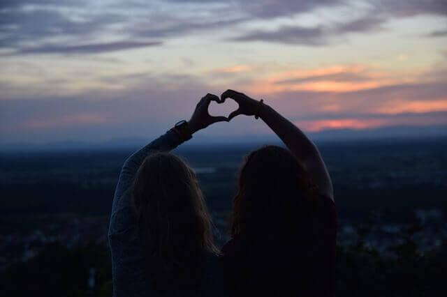 To venner former et hjerte med hendene sine
