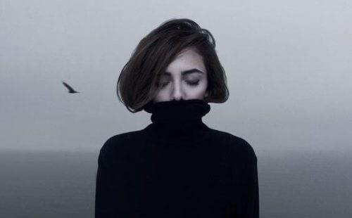 EnIntroversjon med høy-fungerende angst? Bilde av en ung kvinne som lukker øynene og gjemmer seg i en svart høyhalser