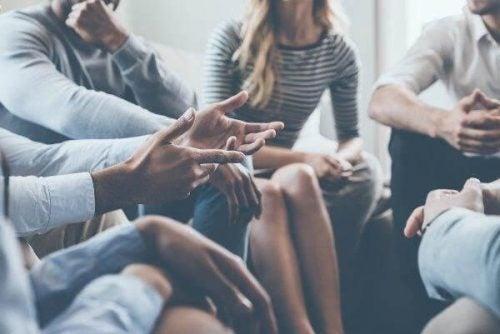 Bildet av en gruppe mennsker som sitter i ring og snakker