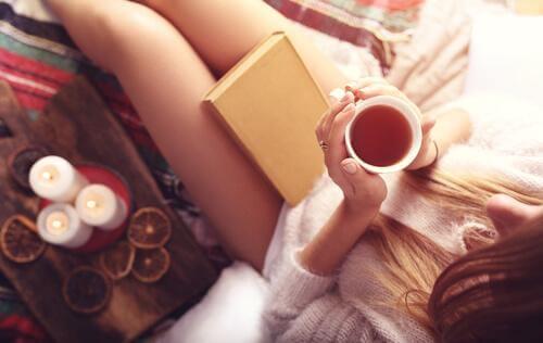 Kvinne sitter med en bok og en kopp te i hånden
