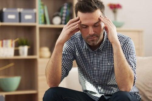 En mann sitter med hodet mellom hendene. Han er sliten av å snakke med andre