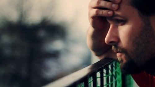 Bildet av en trist ung mann som tar seg til hodet og ser utover et landskap.