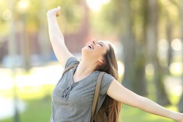 Jente med høy selvfølelse strekker ut armene sine i glede