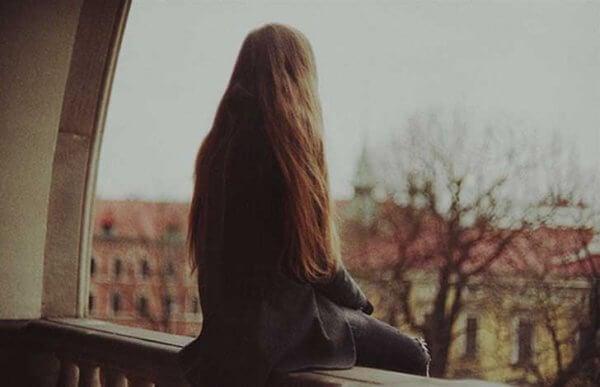 Kvinne sitter på balkongen konfronterer sin ensomhet