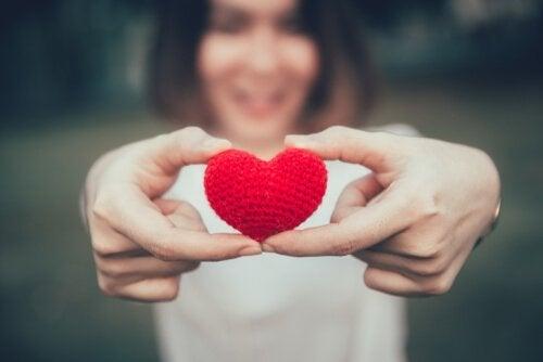 Kvinne holder et lite rødt, strikket hjerte i hendene som hun strekker forran seg i hendene