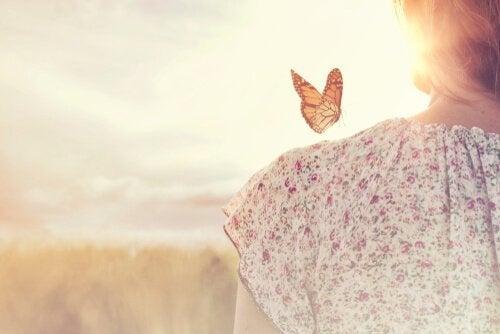 Kvinne med sommerfugl på skulderen som symboliserer en av de 10 lovene om overflod