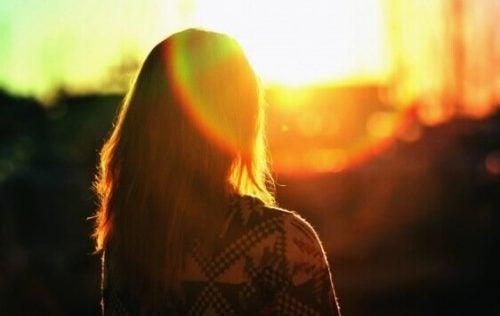 Kvinne ser på solnedgangen