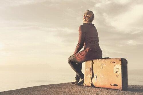Kvinne sitter på en koffert