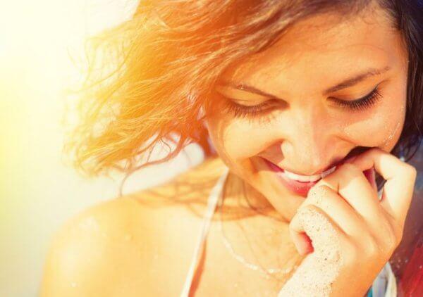 Kvinne smiler for å føle seg lykkeligere