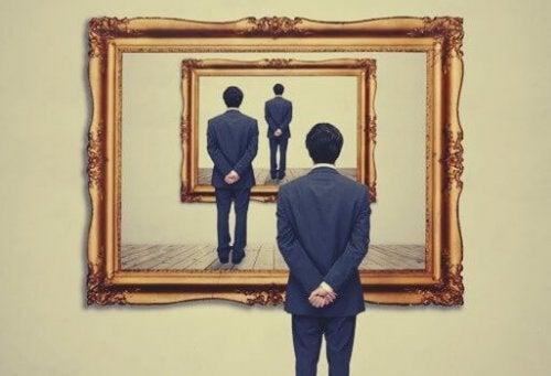 Mann som står forran et speil som reflekteres i andre speil