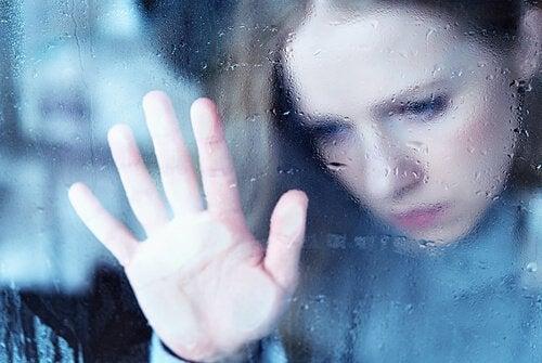 Trist kvinne ser ut av vinduet, konfronterer smerte
