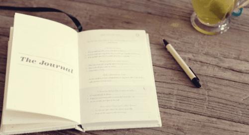 En oppslått dagbok og en blyant på et trebord.