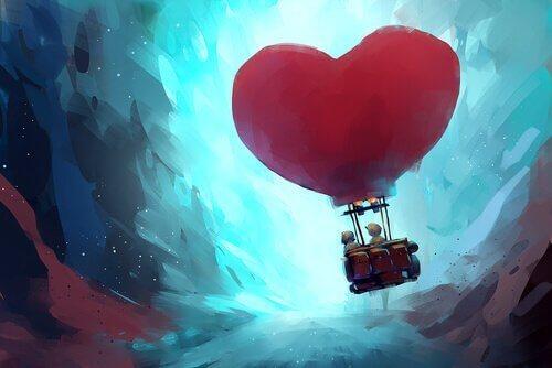 Et par som svever oppover mot himmelen i en kjærlighetsformet lutfabllong