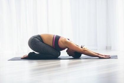 En kvinne gjør yoga om morgenen.