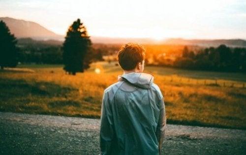En gutt i et felt som vender mot solnedgangen.