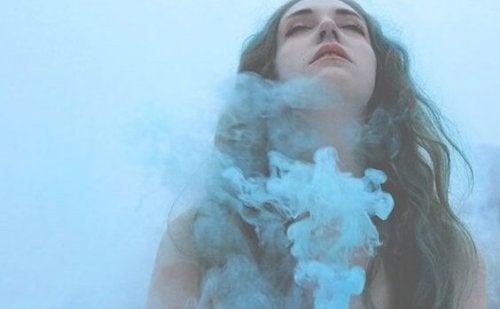 Brunette jente omgitt av blå røyk.