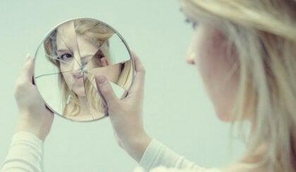 Kvinne ser i et ødelagt speil.