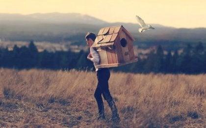 Mann som bærer et fugelhus på ryggen.