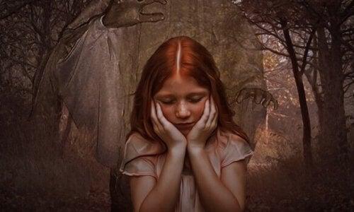 En rødhåret jente foran en skog.