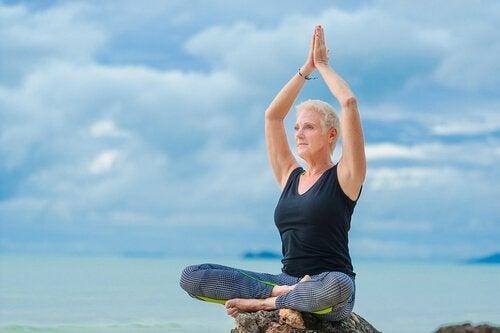 Midorexia - en eldre kvinne sitter på en bergknaus og gjøre yoga.