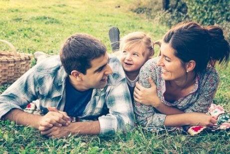 Smilende foreldre med sin lille datter i parken.