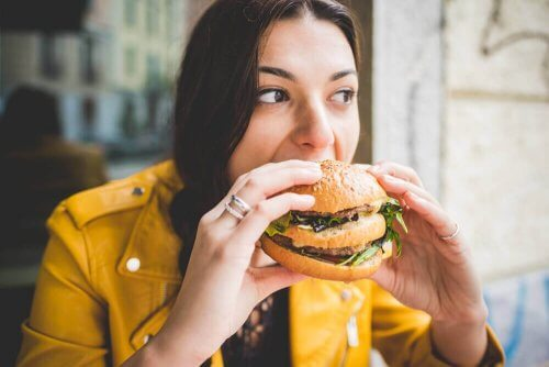 Kvinne spiser en burger