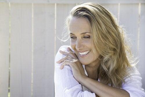 Smilende kvinne i hvit skjorte