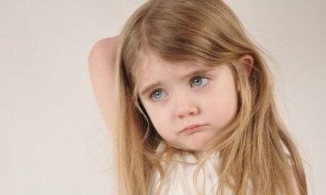 Trist liten jente som kanskje har emosjonelt fraværende foreldre.