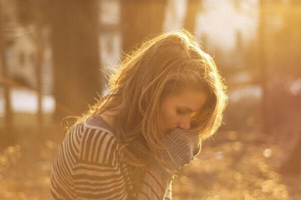 Profilen av en bekymret ung kvinne i sollys