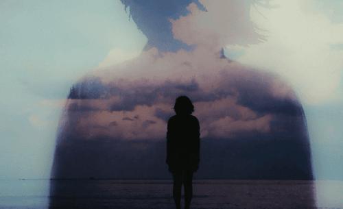 Kvinne i horisonten foran sjøen.