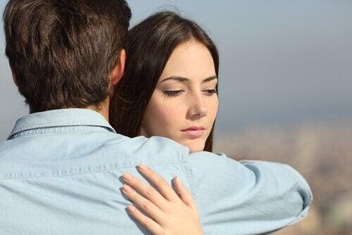 Kvinne klemmer sin venn og tenker på noe annet